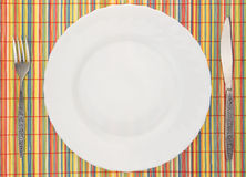 White empty plate with fork and knife on colorful placemat Stock Photography