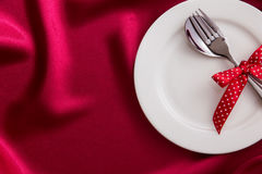 White empty plate with fork and spoon on red silk fabric for Stock Photo