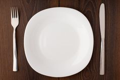 White empty plate, knife and fork served on table Royalty Free Stock Images