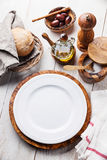 White empty plate and olive wood tableware Royalty Free Stock Photos