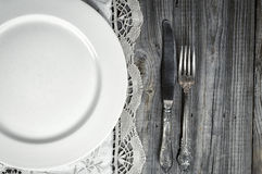 White empty plate on the tablecloth with lace, near knife and fo Stock Image