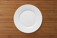 White empty  plate on a wooden table. White clean empty plate on a wooden table Royalty Free Stock Photography