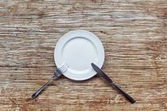 White empty plate on the wooden table Stock Photos