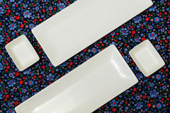 White empty plates on the dark colorful tablecloth. View from above.Example table setting Stock Photo