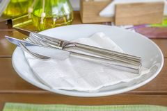 White empty plates with fork and knife on a wooden table royalty free stock photo