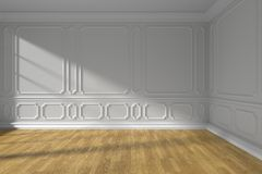 White empty room with molding and wooden floor. White empty room interior with sunlight from window, white decorative classic style molding frames on walls Stock Photo