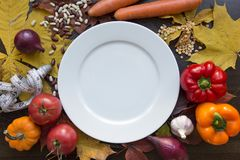White emty plate with measuring tape and vegetables top view. White emty plate with measuring tape and vegetables around background Stock Images