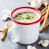 Homemade mushrooms champignons soup. White enamel mug with delicious homemade mushrooms champignons soup with parsley. Healthy food concept Royalty Free Stock Image
