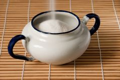 A white enamel sugar bowl being filled Royalty Free Stock Photo