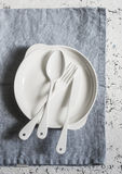 White enameled vintage cutlery and white ceramic plate on a blue  linen napkin on a light background, top view. Stock Photos