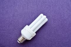 White energy-saving fluorescent light bulb with four tubes, with a silver cap royalty free stock photo