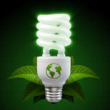 White energy saving light bulb with leafs on black. 3d render of a glowing white energy saving light bulb, surrounded by leafs Royalty Free Stock Image