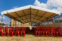 White entertainment tent with red plastic chairs Royalty Free Stock Images