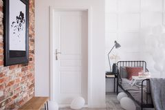 White entrance door to stylish bedroom interior, real photo with copy