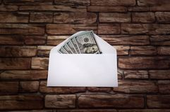 White envelope with five hundred dollar bills in a ray of light against a dark brick wall. White envelope with five hundred dollar bills on the background of a Royalty Free Stock Photos