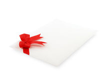 White envelope of invitation or greeting card with simple red ribbon bow isolated on white background. Single white envelope of invitation or greeting card with stock images