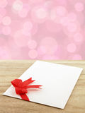 close-up white envelope of greeting card with red ribbon bow on wooden table floor with defocused pink lights bokeh background Royalty Free Stock Photo