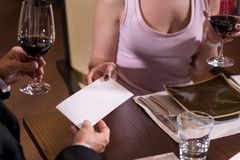 White envelope in hands of a couple in the restaurant. Secret gift. White envelope being in hands of a couple near wineglasses while being under the table in the Stock Photos