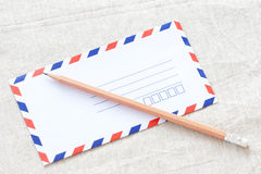 White envelope and pencil on fabric Royalty Free Stock Images