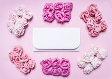 White envelope on a pink background with a tiled around bundles of multicolored roses top view close up place text,frame Royalty Free Stock Image