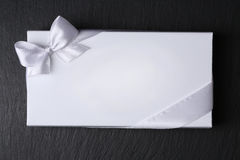White envelope with ribbon on black background Stock Photo