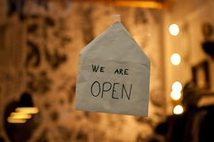 White envelope on a shop window with the words. We are open written on it Royalty Free Stock Image