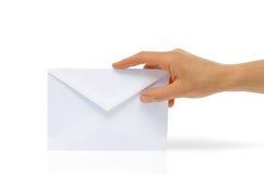 White envelope. Women's hand holding an envelope on a white background Stock Photo