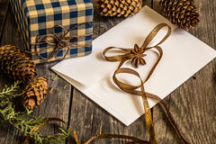 White envelope on wooden background with pine cones and Christmas gift Royalty Free Stock Photography