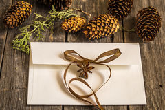 White envelope on wooden background with pine cones and Christmas gift Stock Images