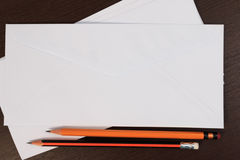 White envelopes with pencil on wooden table. Royalty Free Stock Image