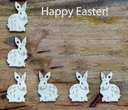 White bunnies on wooden background copyspace. White esater bunnies lined up at the side and base of wooden copyspace, facing the same direction or each other Royalty Free Stock Images