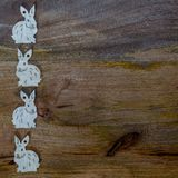 White bunnies on wooden background copyspace. White esater bunnies lined up at the side of wooden copyspace, facing opposite directions - easter background Stock Photography