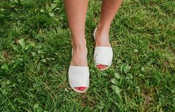 White espadrilles with open toe on female legs. womens shoes.  royalty free stock photos