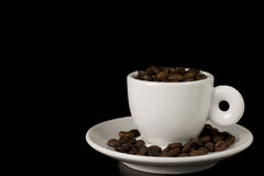 White espresso cup. Filed to the brim with coffee beans Stock Photo
