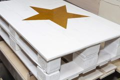 White Euro pallet table decorated with bright yellow star.  royalty free stock photography