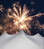 White events tent beneath fireworks. A white events tent with three peaks beneath exploding fireworks in the night sky royalty free stock images