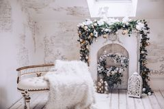 White exclusive sofa with gilding on the background of the fireplace. Christmas decorations from Christmas tree branches and toys. White exclusive sofa with Royalty Free Stock Images