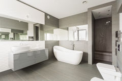 White exclusive washroom. White and grey exclusive big washroom with fancy bath stock images