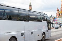 White excursion bus moves in the center of Moscow. Near the Kremlin. Side view Royalty Free Stock Images