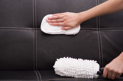 White fabric brush from steam cleaning machine being used on black leather couch, hand rubbing sofa with cloth Royalty Free Stock Image