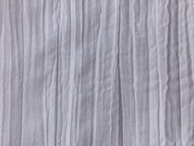 White fabric with a crumpled effect and vertical creases. White background with crumpled fabric structure stock photo