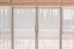 White fabric curtain. Transparent soft white fabric curtain on grass door of modern building, see through balcony and pine garden outside view background Royalty Free Stock Images
