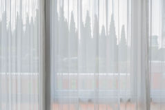 White fabric curtain. Transparent soft white fabric curtain on grass door of modern building, see through balcony and pine garden outside view background Royalty Free Stock Photos