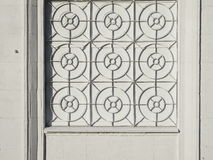 White facade of the house with a wrought iron grating on the window royalty free stock photo