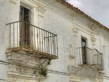 Facade of old building in Spanish town. White facade of old building with two balconies in Spanish town Stock Photography