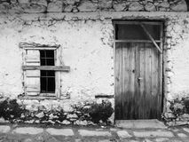 Facade of an old building with doors and a window in Crete, Greece. White facade of an old house with old wooden doors and a window with steel bars in Crete Stock Images