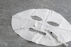 White facial mask and clean syringe on grey table.Concept of face lift stock image