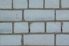 White faded old bricks background with flaws and splits. On it surface stock photography
