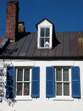 White Family Home. View of a white family home, white walls, blue shutters, brick roof Stock Images