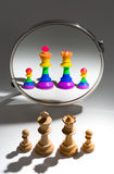 A white family is looking in a mirror to see themselves covered with a rainbow flag. A white family of four chess pieces is looking in a mirror and sees Stock Photo